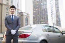 Motorista chinês de pé ao lado do carro — Fotografia de Stock