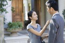 Giovane donna cinese regolazione cravatta uomo sulla strada — Foto stock