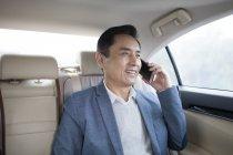 Asian man talking on phone on car back seat — Stock Photo