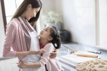 Chinese mother and daughter embracing while making dumplings — Stock Photo