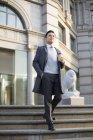 Chinesischer Geschäftsmann geht mit Kaffee in der Stadt die Treppe hinunter — Stockfoto
