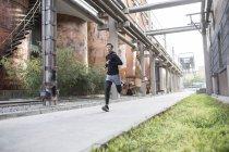 Athlète masculin chinois, faire du jogging sur la rue — Photo de stock
