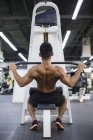 Young man exercising at gym equipment — Stock Photo