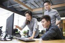 Китайские офисные работники используют компьютер в офисе — стоковое фото