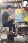 Азіатський чоловічого художник працює в арт-студії — стокове фото