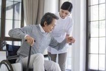Assistant infirmier chinois prenant soin de l'homme âgé en fauteuil roulant — Photo de stock