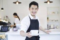 Chinesischer Coffeeshop-Besitzer hält Tasse Kaffee — Stockfoto