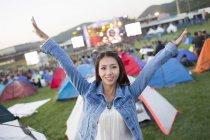 Mujer china con los brazos levantados posando con el festival de camping en el fondo - foto de stock