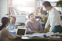 Архитекторы, работающие и разговаривающие в офисе — стоковое фото