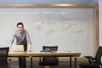 Chinese man using standing with laptop in board room — Stock Photo