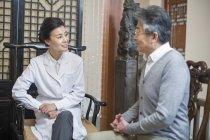 Médico chino mujer hablando con el paciente masculino - foto de stock