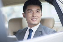 Chinese businessman sitting on car back seat and looking through window — Stock Photo