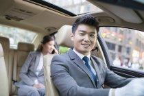 Chinois avec chauffeur au volant de voiture avec une femme d'affaires, parler au téléphone sur le siège arrière — Photo de stock