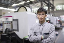 Confident Chinese engineer with arms crossed at factory — Stock Photo