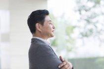Asiático empresário de pé com braços dobrados — Fotografia de Stock