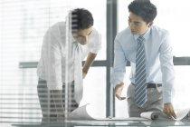 Китайские бизнесмены обсуждают план работы на рабочем месте — стоковое фото