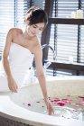 Молода Китайська жінка, що сидить ванною з пелюстками троянд — стокове фото