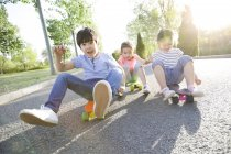 Китайські діти, що сидять їхав на скейтборд — стокове фото