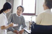 Chinesische Krankenschwester spricht mit einem älteren Mann und schreibt in Klemmbrett — Stockfoto