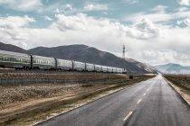 Train au chemin de fer le long de l'autoroute au Tibet, Chine — Photo de stock