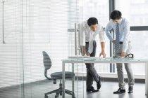 Chinesische Geschäftsleute sprechen im Büro innen — Stockfoto