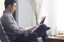 Молодой человек, работающий с ноутбуком в офисе — стоковое фото