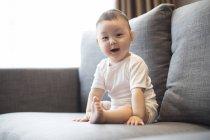 Bambino cinese seduto sul divano e guardando in macchina fotografica — Foto stock