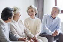 Senior Chinese friends talking on sofa in living room — Stock Photo