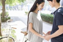 Chinese couple holding hands at campus with bicycle — Stock Photo