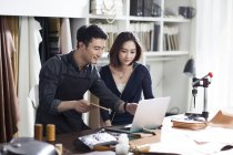 Asian craftsman and customer in studio with laptop — Stock Photo