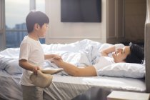 Chinese boy with slippers waking up parents in bedroom — Stock Photo