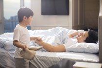 Китайский мальчик в тапочках разбудил родителей в спальне — стоковое фото