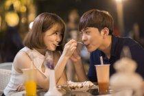 Giovani coppie cinesi d'alimentazione l'altro gelato nella caffetteria — Foto stock