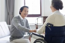 Senior Chinese man taking care of senior woman in wheelchair — Stock Photo