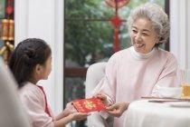 Китайская бабушка, давая красный конверт для внучки — стоковое фото