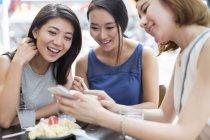 Female friends using smartphone at sidewalk cafe — Stock Photo