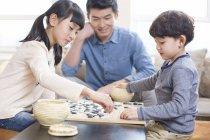 Bambini guardare uomo asiatico giocando Go giochi a casa — Foto stock