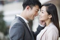 Chinese couple standing face to face and smiling — Stock Photo