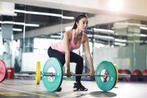 Азиатка поднимает штангу в спортзале — стоковое фото