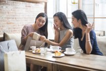 Mulher chinesa demonstrando novas roupas para amigas no café — Fotografia de Stock