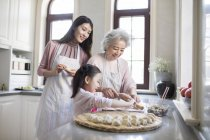 Chinese family making dumplings in kitchen — Stock Photo