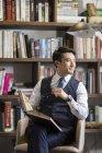 Asiático hombre de negocios leyendo libro en estudio - foto de stock