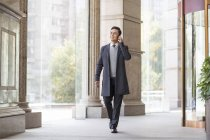 Chinese businessman walking and talking on phone in city — Stock Photo