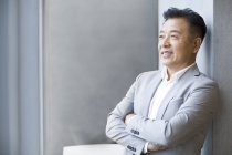 Chinese businessman looking through window in office — Stock Photo
