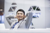 Chinese businessman sitting with hands behind head in office — Stock Photo