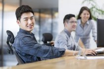 Chinese office workers sitting in office — Stock Photo
