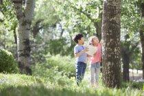 Китайські діти вивчають стовбур дерева в лісі — стокове фото