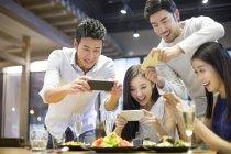 Asiatische Freunde die Fotos von Essen beim Abendessen im restaurant — Stockfoto
