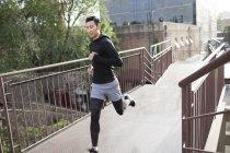 Chinois jogging sur le pont en ville — Photo de stock