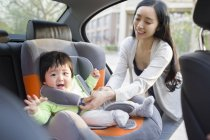 Asian mother fastening seat belt for toddler daughter — Stock Photo